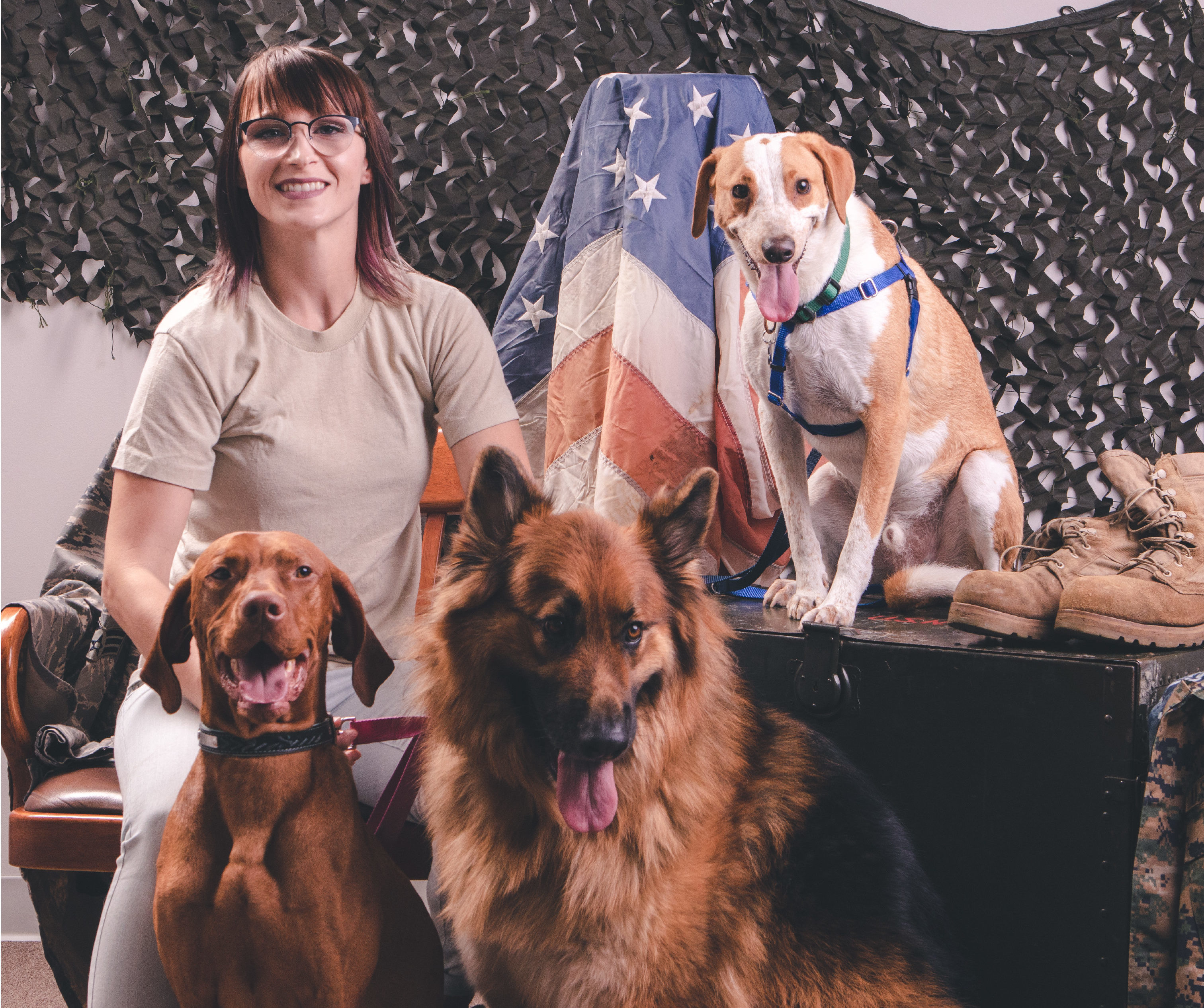 female veteran sitting with three different breeds of dogs